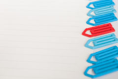 Paper clip on a white paper. Many blue and one red paper clip on a white paper  with space for text Stock Images