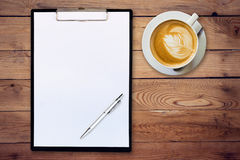 Paper clipboard and coffee on wood background with space Stock Image