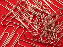 Paper Clips. A pile of paper clips on a red background. Focus is on the center clips, with a shallow depth of field - focus softens on the outer clips stock image