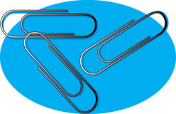 Paper Clips. Three metal paper clips on a blue background Stock Photo