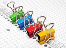 Paper Clips. Group of four colored paper clips on squared paper Royalty Free Stock Photography