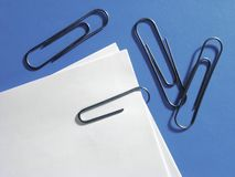 Paper clips. One paper clip holding papers together and three separate paper clips; blue background Royalty Free Stock Photos