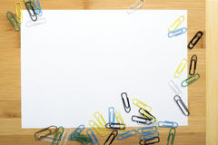 Paper clips and blank paper on wooden background Royalty Free Stock Images