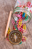 Paper clips in bottle,pencil and compass on a wooden background. Stock Photo