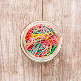 Paper clips in bottle on a wooden background Royalty Free Stock Photography