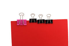 Paper clips on a red background. Three black and one big paper clip on sheet of red colour Stock Photo