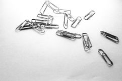 Paper clips on white background. Paperclips scattered on a white background stationery metal office in a different order Royalty Free Stock Photography