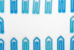 Paper clips on a white paper. Many blue paper clip on a white paper sheet with space for text Royalty Free Stock Image