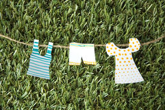 Paper clothes on green grass Royalty Free Stock Photos
