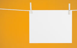 Paper on the Clothesline. Blank piece of paper hanging from a rope with a yellow-gold background stock photography