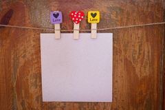 Paper with clothespins with hearts hanging from a rope Stock Photos