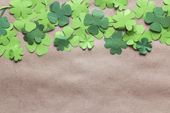 Paper clover leaves on the brown paper background. Lucky shamrock. Space for text. stock photos