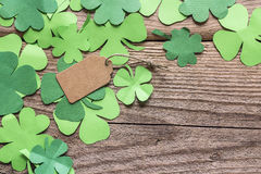 Paper clover leaves with empty brown label on the old wooden background. Space for text, stock photo