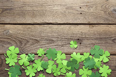 Paper clover leaves on the old wooden background. Lucky shamrock Stock Photography
