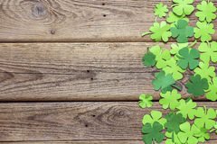 Paper clover leaves on the old wooden background. Space for text. Paper clover leaves on the old wooden background. Lucky shamrock, St. Patrick`s day holiday royalty free stock images