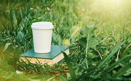 Paper coffee cup and book in grass Royalty Free Stock Image