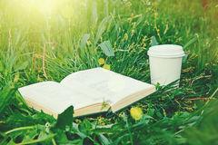 Paper coffee cup and book in grass Royalty Free Stock Photo