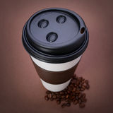 Paper Coffee cup with Coffee Beans on brown background. Takeaway Stock Photo