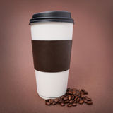 Paper Coffee cup with Coffee Beans on brown background. Takeaway Stock Image
