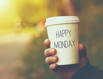 Paper coffee cup Happy Monday. Hand holding paper cup of coffee with Happy Monday motivational text on natural morning background Royalty Free Stock Photography