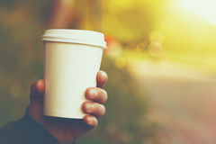 Paper coffee cup outside. Hand holding paper cup of coffee on natural morning background Stock Photo