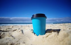 Paper coffee cup in the sand at the beach Royalty Free Stock Images