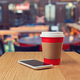 Paper coffee cup and smart phone. Over blur street background royalty free stock photos