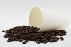 Paper coffee cup with spilled coffee beans, white background. Coffee beans stock images