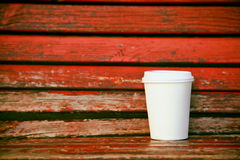 Paper coffee cup on wooden bench Royalty Free Stock Photography