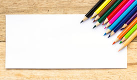 Paper and color pencils on table Stock Photos