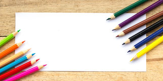 Paper and color pencils on table Stock Photography