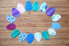 Paper colored Easter eggs are arranged with an oval frame, on a wooden board Stock Photos