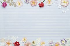 Paper colored flowers on the edges, blue background with stripes and blank space in the center. Top view stock photos