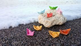 Paper colored on a rock. Paper boats rock beach kids childhood colour toh toy sea sand children papership paperboat simile simple white abstract origami vincent royalty free stock photography