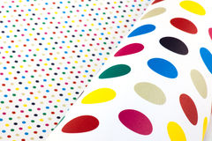 Paper with colorful dots. White paper with small dots and in a roll with large spots royalty free stock photo