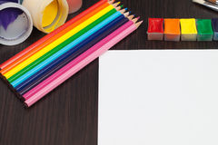 Paper with colorful pencils and paints Royalty Free Stock Image