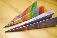 Paper colorful planes on a wood table Royalty Free Stock Photography