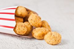 Paper container with fried crispy chicken popcorn. Nuggets on wooden background stock photo