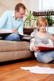 Paper couple finance family. Scenic young family couple at home indoors in living room doing paperwork sitting on couch and floor with lot of paper documents Stock Photography