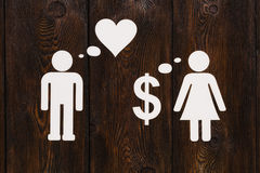 Paper couple, love vs money. Abstract conceptual image Royalty Free Stock Image