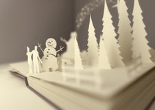 Paper Craft Christmas Story. Pop-Up Book - Christmas Story. Styled 3D pop-up book with a christmas theme including a family building a snowman, winter forest and Stock Photos