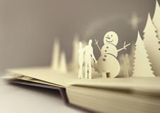 Paper Craft Christmas Story. Pop-Up Book - Christmas Story. Styled 3D pop-up book with a christmas theme including a family building a snowman, winter forest and Royalty Free Stock Photo