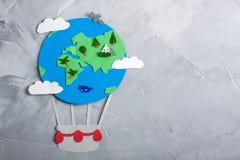 Paper craft earth globe handmade on gray concrete background. Stock Photo