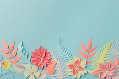 Paper craft origami fower decoration creative idea. tropical Flowers and leaves on blue pastel background, summertime, evegreen. Modern trendy concept stock photo