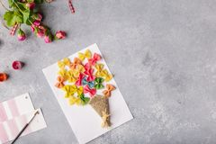 Paper crafts for mother day, 8 march or birthday. Small child doing a bouquet of flowers out of colored paper and colored pasta. stock photo