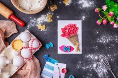 Paper crafts for mother day, 8 march or birthday. Small child doing a bouquet of flowers out of colored paper and colored pasta. royalty free stock images