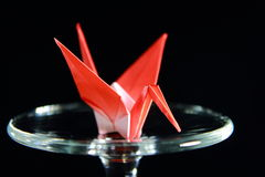 Paper crane on glass table isolated on black background. Red paper crane on glass table isolated on black background Royalty Free Stock Image