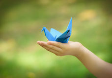 Paper crane on little girl's hand Stock Photos