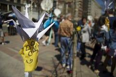 "Paper Crane and Yellow Ribbon. Boston, Massachusetts USA - April 2013 - Origami Crane ""Birds of Happiness"" with yellow prayer ribbon tied below it at the Boston Royalty Free Stock Image"