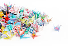 Paper cranes. A paper crane standing out from a pile of paper cranes royalty free stock images
